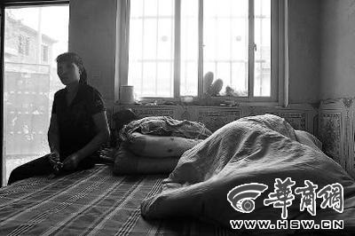 凯凯在网吧玩通宵后,下午两点还在睡觉,用被子把自己包裹严实,坐在一旁的母亲一脸无奈 本报记者 赵国强 摄