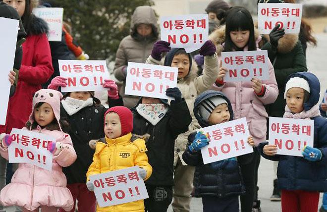 """一群韩国小朋友在家长的带领下,手举""""儿童暴力NO!!""""的口号"""